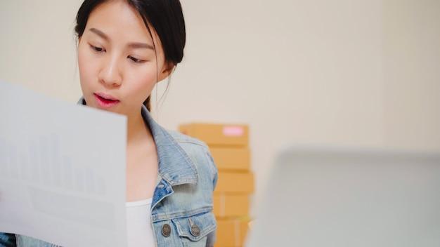 Hermosa joven empresaria asiática inteligente, dueña de una mujer de negocios en línea que comprueba el producto en stock y la guarda en el equipo que trabaja en casa.