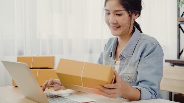 Hermosa joven empresaria asiática inteligente, dueña de una mujer de negocios en línea que comprueba el producto.