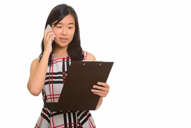 Hermosa joven empresaria asiática leyendo el portapapeles mientras habla por teléfono móvil