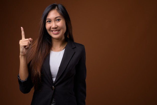 Hermosa joven empresaria asiática sobre fondo marrón