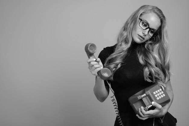 Hermosa joven empresaria con cabello rubio contra la pared gris en blanco y negro