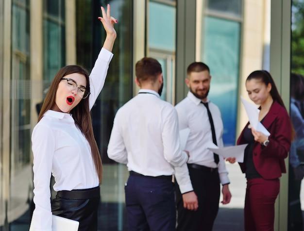 Hermosa joven empresaria es feliz en el contexto de un edificio de oficinas y colegas