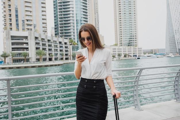 Hermosa joven empresaria moderna de pie en un dubai marine y mirando su teléfono con barra de maleta en una mano.
