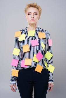 Hermosa joven empresaria con notas post-it por todo su aislado