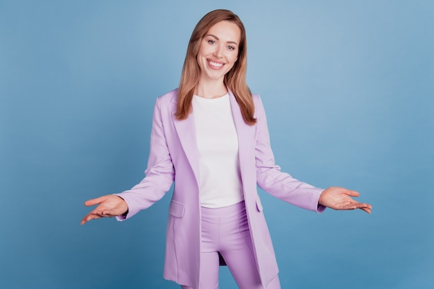 Hermosa joven empresaria sonriendo con los brazos abiertos bienvenida aislado sobre fondo azul.