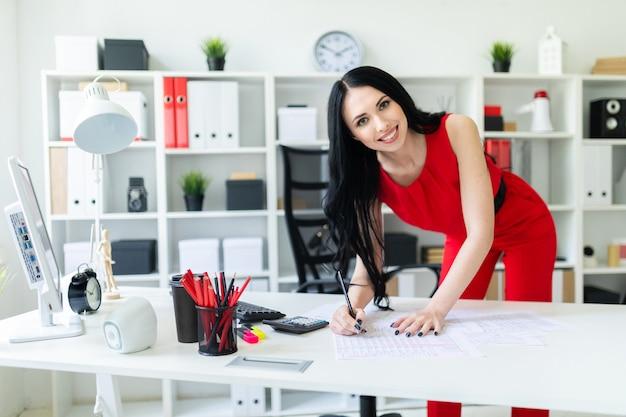 Una hermosa joven se encuentra cerca de un escritorio de oficina. la mujer trabaja con documentos, calculadora y computadora.