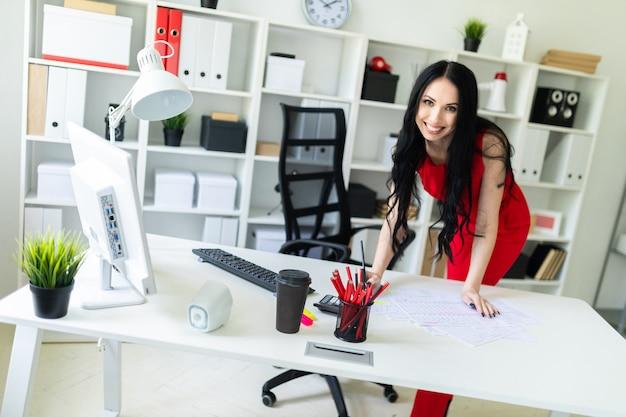 Una hermosa joven se encuentra cerca de un escritorio de oficina.
