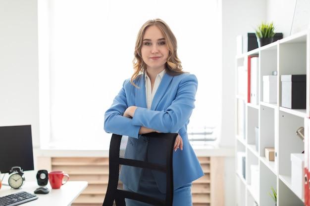 Una hermosa joven se encuentra cerca de un estante en la oficina, apoyando los codos en el respaldo de una silla.