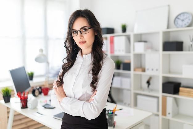 Una hermosa joven se encuentra cerca de la mesa de la oficina, con las manos cruzadas sobre su pecho.