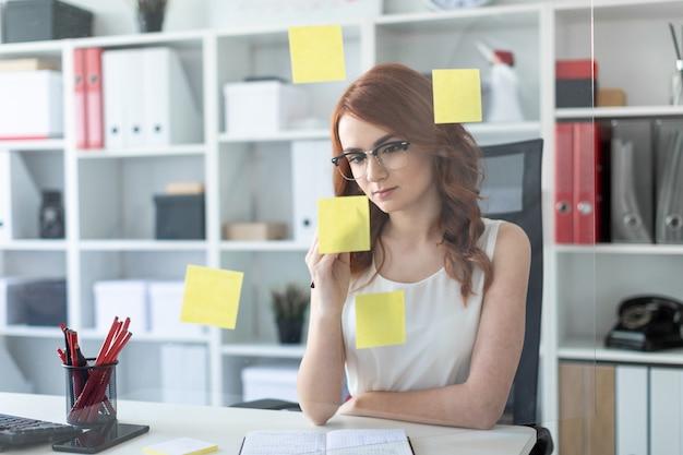 Una hermosa joven se encuentra en la oficina cerca de un vaso en el que se pegan pegatinas.