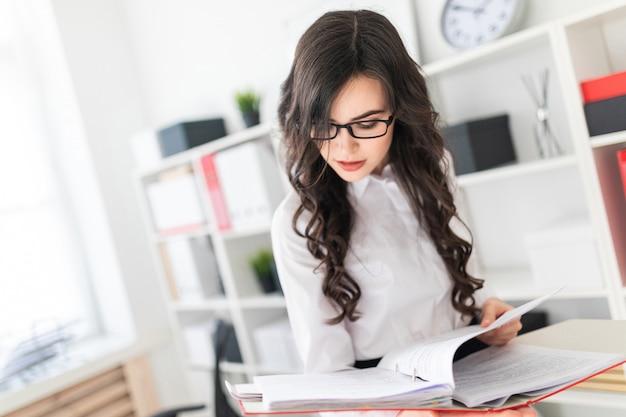 Hermosa joven se encuentra en la oficina pulgares una carpeta con documentos.