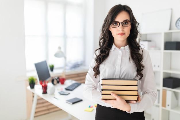 Hermosa joven se encuentra en la oficina y tiene una pila de libros en sus manos.