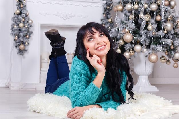 Hermosa joven se encuentra en el suelo en el interior en un interior de navidad
