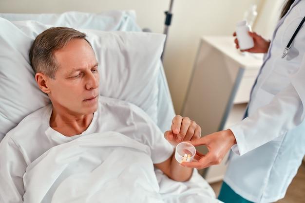 Una hermosa joven enfermera le da un medicamento a un paciente masculino maduro, que está acostado en una cama en una moderna sala de hospital.