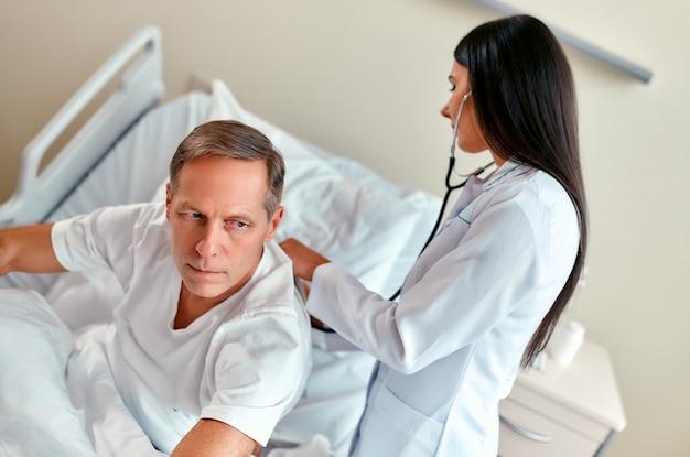 Una hermosa joven enfermera revisa los pulmones de un paciente maduro con un estetoscopio, yace en una cama en una sala moderna.