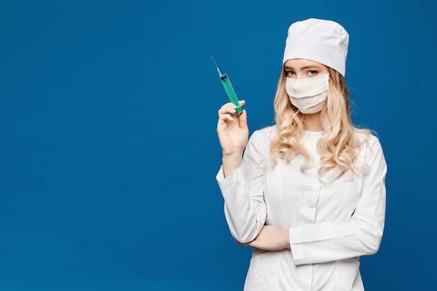 Hermosa joven enfermera en traje médico con jeringa. inyección médica. doctor bastante joven con una jeringa. concepto de farmacia y medicina