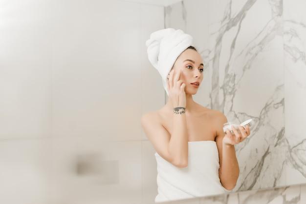 Hermosa joven envuelta en toallas usa crema para la cara en el baño