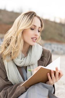 Hermosa joven escribiendo en el cuaderno sentado en la playa con un traje elegante