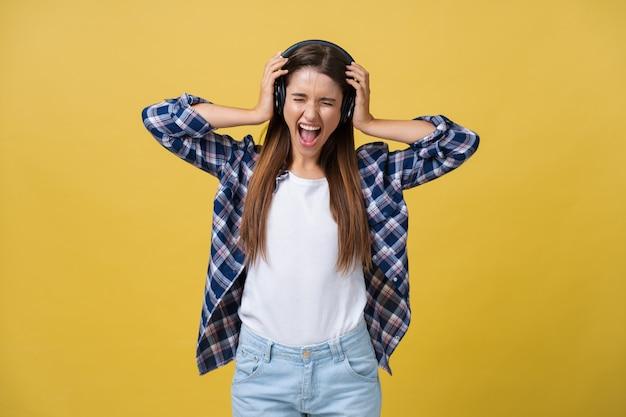 Hermosa joven escuchando música en auriculares sobre fondo de color