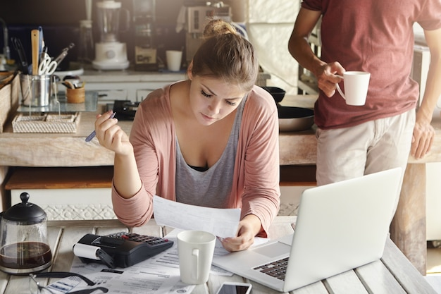 Hermosa joven esposa planificación del presupuesto doméstico, recortando los gastos familiares