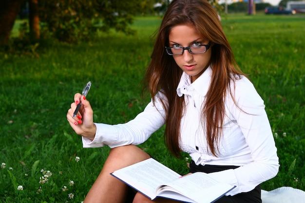 Hermosa joven estudiando en el parque