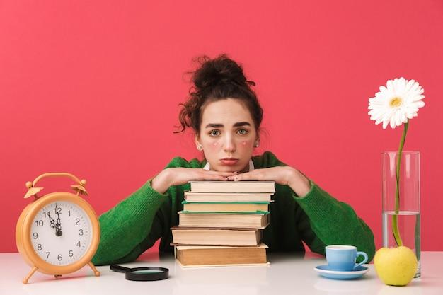 Hermosa joven estudiante aburrida sentada en la mesa aislada, estudiando con libros