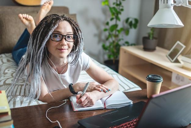 Una hermosa joven estudiante con rastas está estudiando en una lección en línea en casa en una habitación con una computadora portátil