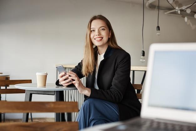 Hermosa joven estudiante sentarse en la cafetería y con smartphone