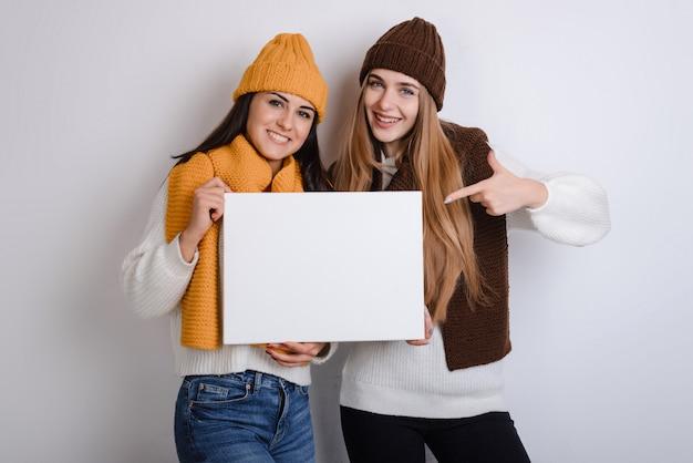 Una hermosa joven estudiante con tiene una hoja en blanco cuadrado blanco en sus manos.