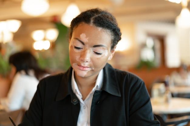 Una hermosa joven de etnia africana con vitiligo sentado en un restaurante.