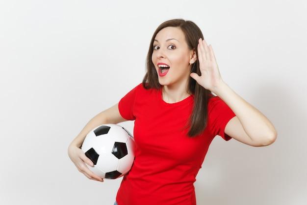 Hermosa joven europea, aficionado al fútbol o jugador en uniforme rojo escucha a escondidas, escucha el gesto, sostiene el balón de fútbol aislado sobre fondo blanco. deporte jugar fútbol, salud, concepto de estilo de vida saludable.