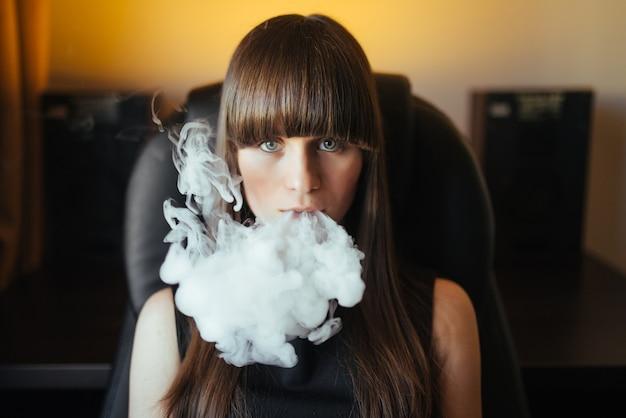 Hermosa joven exhalando humo de una pipa de agua y mirando a la cámara