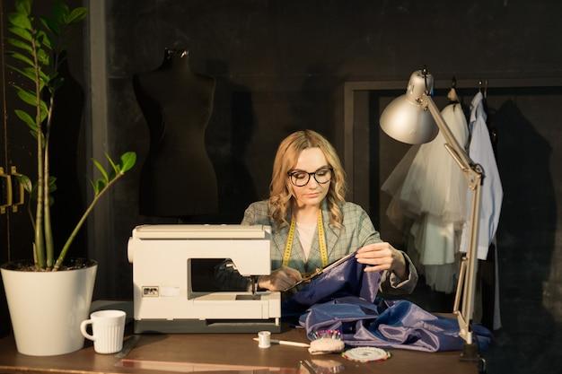 Hermosa joven en una fábrica con una máquina de coser en la mesa