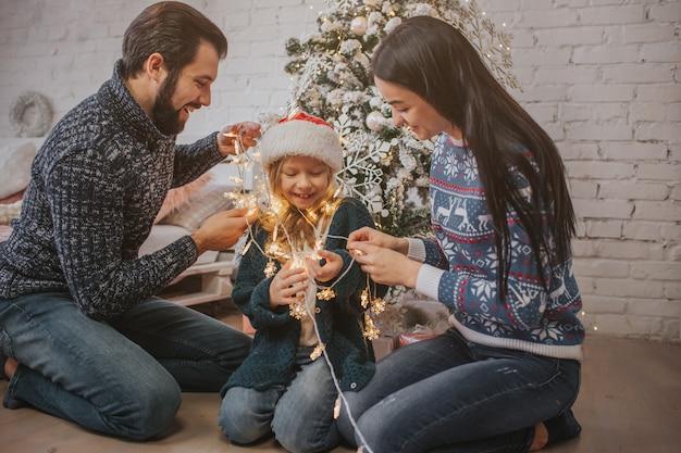 Hermosa joven familia disfrutando de sus vacaciones juntos, decorando el árbol de navidad, arreglando las luces navideñas y divirtiéndose