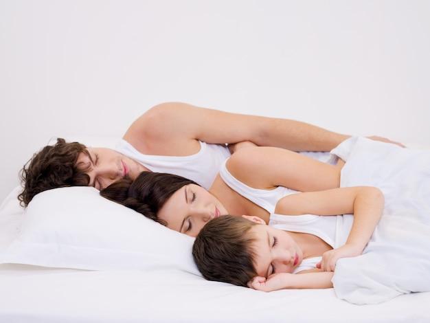 Hermosa joven familia durmiendo con el pequeño hijo