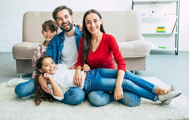 Hermosa joven familia feliz sentada en el suelo en casa y divertirse