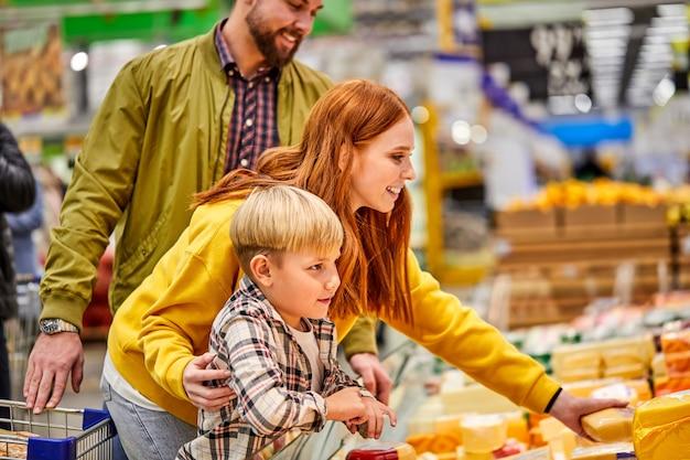 Hermosa y joven familia haciendo compras juntos