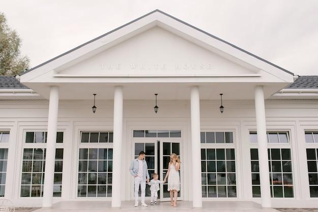 Hermosa joven familia hombre mujer e hijo en ropa elegante en el fondo de una lujosa casa blanca