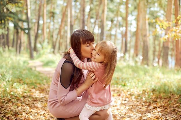 Hermosa joven familia de una madre embarazada y su hija, sonriendo la besa en la mejilla, caminar en el otoño en un parque forestal en un día soleado.