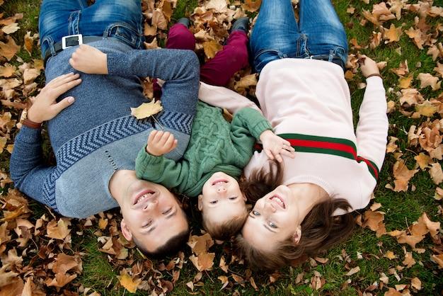 Hermosa joven familia en un paseo en el bosque de otoño.