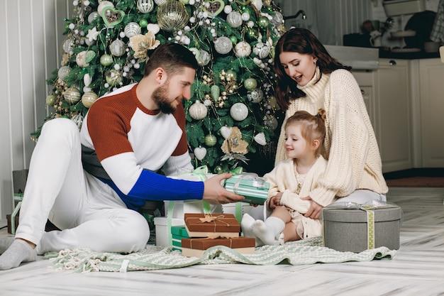 Hermosa joven familia sentada junto a un árbol de navidad muy bien decorado