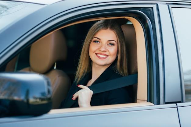Hermosa joven feliz abrocha un cinturón de seguridad en el coche