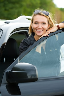 Hermosa joven feliz en el coche nuevo - al aire libre