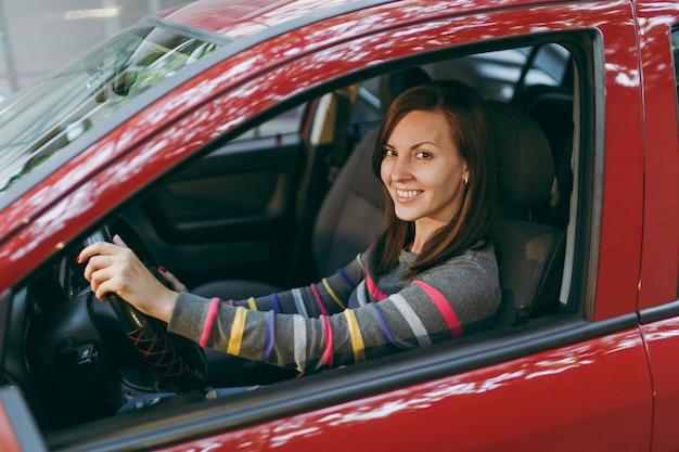 Una hermosa joven feliz sonriente europea de pelo castaño con piel limpia y sana vestida con una camiseta a rayas se sienta en su coche rojo con interior negro. concepto de viaje y conducción.