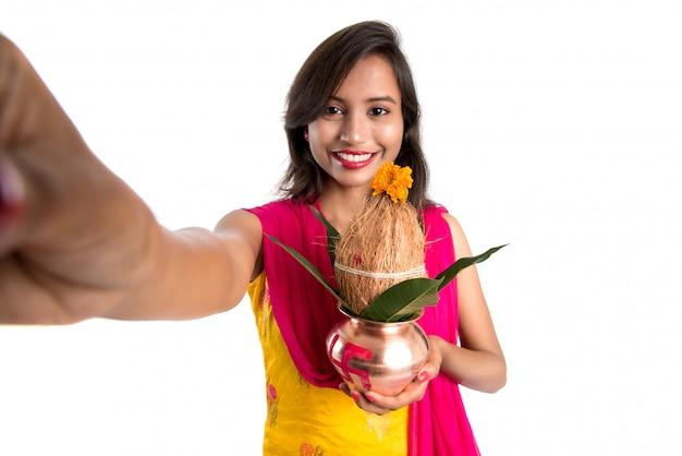 Hermosa joven feliz tomando selfie con kalash usando una cámara o teléfono inteligente