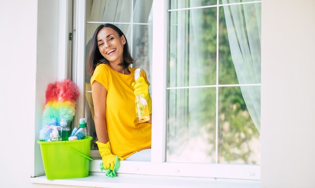 Hermosa joven feliz está usando un plumero y un spray mientras limpia una ventana en la casa