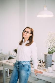 Hermosa joven femenina en elegantes gafas vestidas con ropa casual de moda en una habitación luminosa con flores frescas