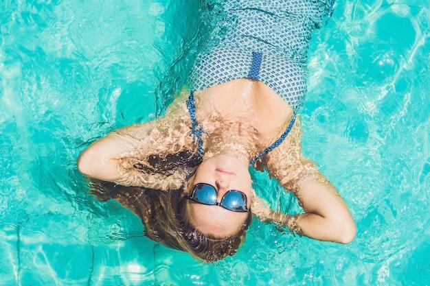 Hermosa joven flotando en la piscina relajante vista superior