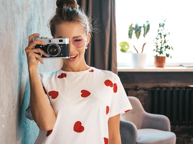 Hermosa joven fotógrafo sonriente chica tomando fotos con su cámara retro. mujer haciendo fotos.