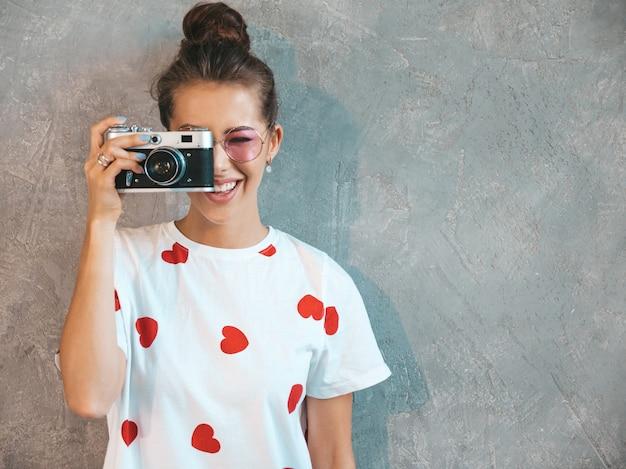 Hermosa joven fotógrafo sonriente chica tomando fotos con su cámara retro.